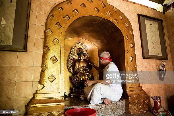 Balinese man cleans a Buddha statue during preparations for the upcoming Chinese New Year at Dwipayana Tanah Kilap Temple on January 25 2014 in...