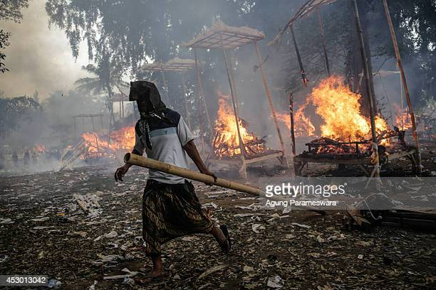 Balinese man holds a bamboo to control the fire during Balinese Hindu mass cremation on August 1 2014 in Ubud Bali Indonesia More than 100 corpses...