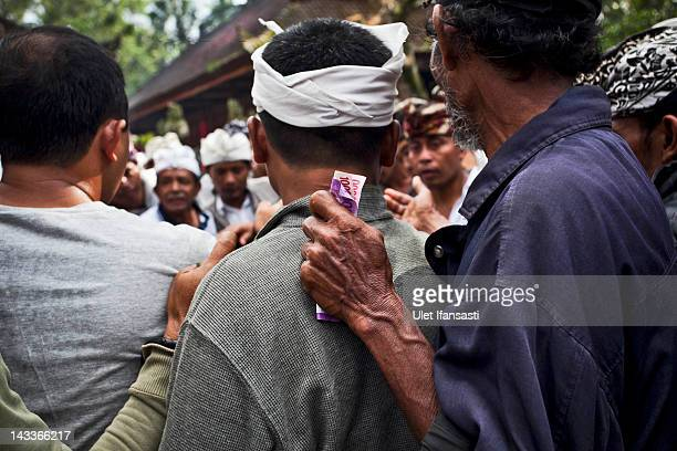 A balinese man holds money during the sacred 'Aci Keburan' ritual at Nyang Api Temple on February 12 2012 in Gianyar Bali Indonesia Cockfighting in...