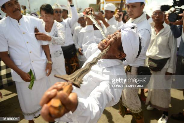 Balinese man in a trance holds daggers to his cheeks during a Melasti ceremony prayer at Petitenget beach near Denpasar on Indonesia's resort island...