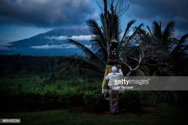 KARANGASEM BALI INDONESIA SEPTEMBER 29 A balinese man prays as mount Agung is in the backround on September 29 2017 in Karangasem regency Island of...
