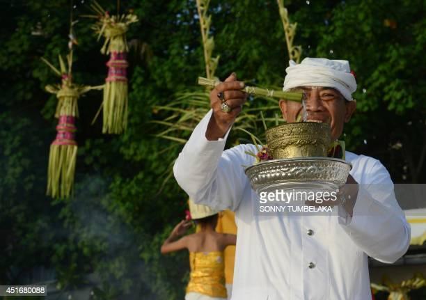A Balinese man prays near a beach during Melasti ceremony prayers in Kuta on Bali island on July 4 2014 During Melasti villagers dressed in their...