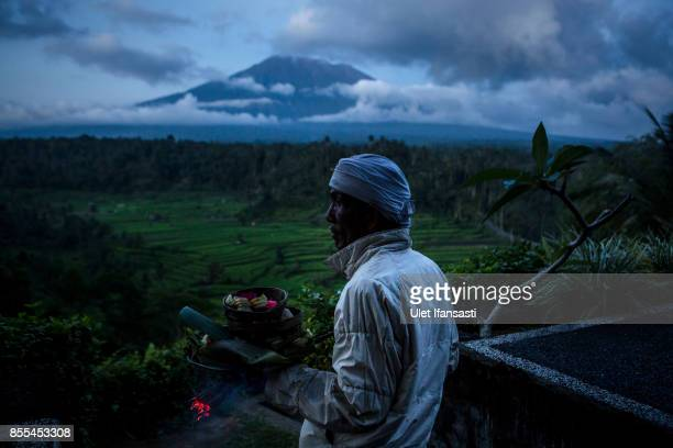 KARANGASEM BALI INDONESIA SEPTEMBER 29 A balinese man prepares for pray with mount Agung in the backround on September 29 2017 in Karangasem regency...