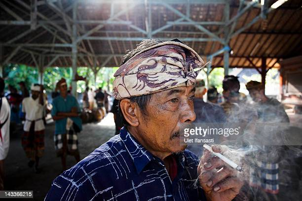 Balinese man smokes during the sacred 'Aci Keburan' ritual at Nyang Api Temple on February 13 2012 in Gianyar Bali Indonesia Cockfighting in Bali...