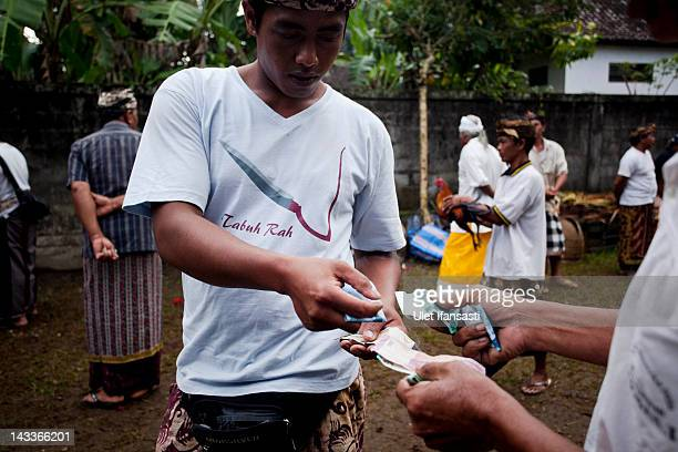 Balinese men make a transaction at the end of a cockfight during the sacred 'Aci Keburan' ritual at Nyang Api Temple on February 16 2012 in Gianyar...