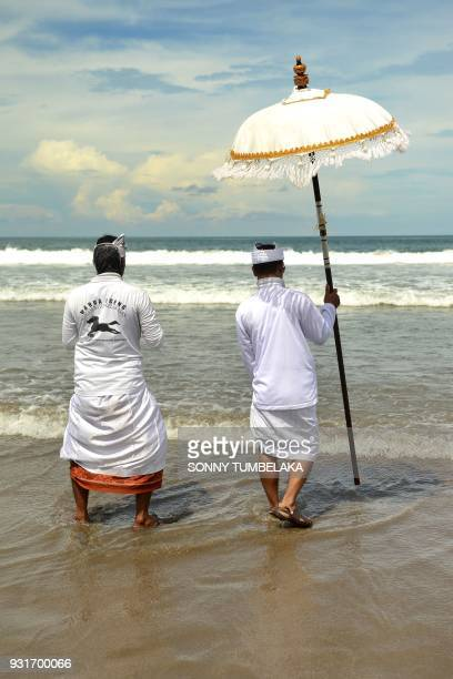 Balinese men walk along the shore during a Melasti ceremony prayer at Petitenget beach near Denpasar on Indonesia's resort island of Bali on March 14...