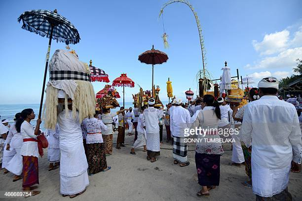 Balinese people carry offerings during the Melasti ceremony prayer at Kuta beach on the island of Bali on March 18 2015 Melasti is a purification...