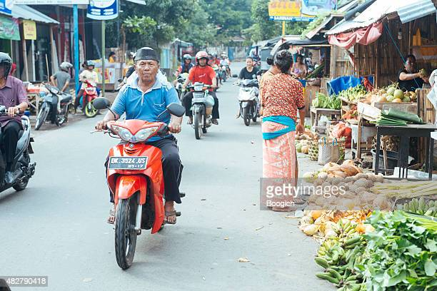 Balinese People Driving Through Traditional Indonesian Street Market Rural Scene