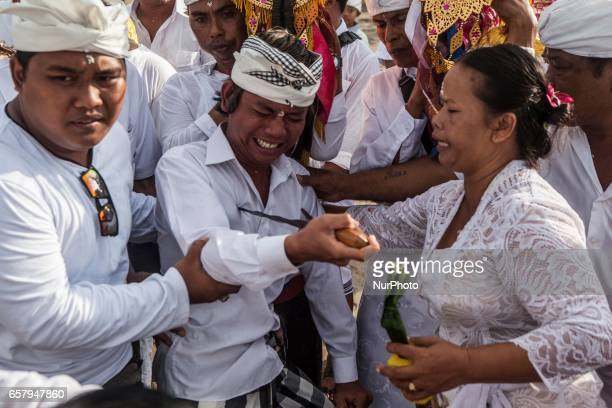 A Balinese people in a trance stabs himself with a 'keris' traditional dagger during Melasti prayer ceremony at Petitenget beach in Bali Indonesia on...