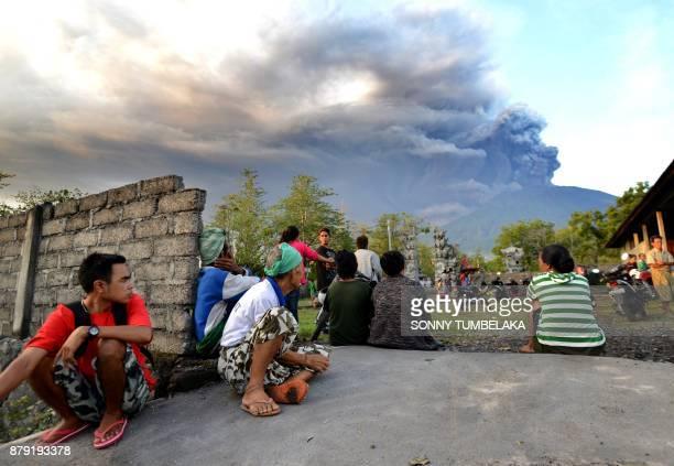Balinese people look at Mount Agung during an eruption seen from Kubu subdistrict in Karangasem Regency on Indonesia's resort island of Bali on...