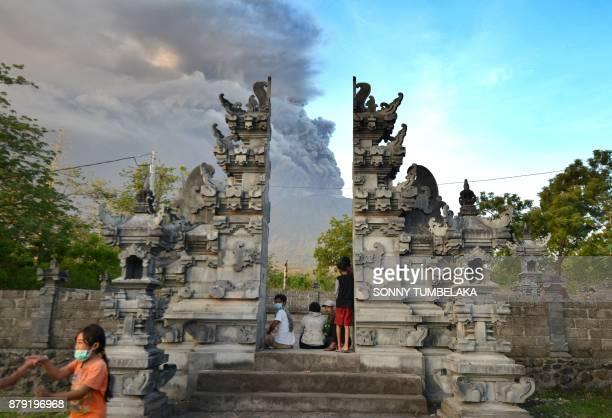 TOPSHOT Balinese people look at Mount Agung during an eruption seen from Kubu subdistrict in Karangasem Regency on Indonesia's resort island of Bali...