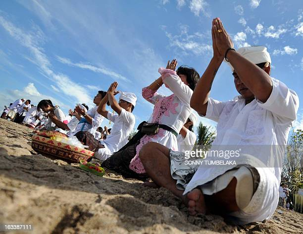 Balinese people pray during a Melasti ceremony at Kuta beach on Indonesia's resort island of Bali on March 9 2013 Melasti is a purification festival...