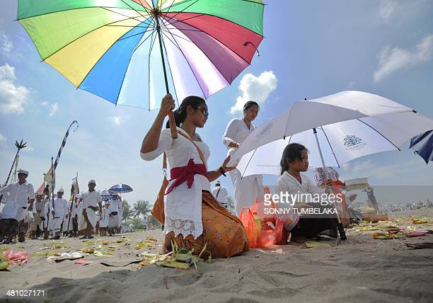 Balinese people pray during a Melasti ceremony prayer session at Petitenget beach in Kuta on Indonesia's resort island of Bali on March 28 2014...