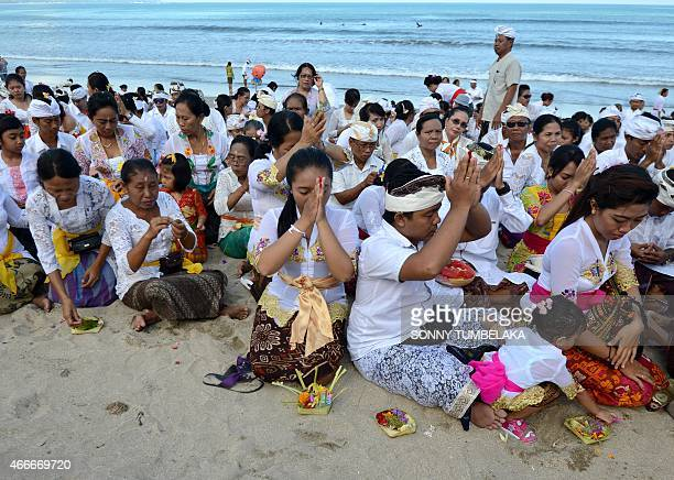 Balinese people pray during the Melasti ceremony at Kuta beach on the island of Bali on March 18 2015 Melasti is a purification festival which is...
