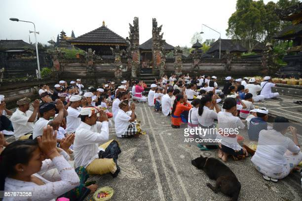 Balinese people pray for Mount Agung at Besaki tempel during Purnama ceremony as Mount Agung is seen obscured by clouds in Karangasem on Bali island...