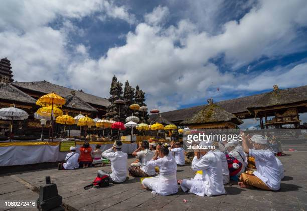 balinese people praying in a temple pura besakih, bali, indonesia. - shaifulzamri stock pictures, royalty-free photos & images