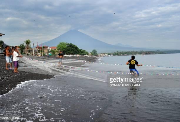 Balinese people pull their fishing net on Amed beach as Mount Agung volcano belches ash in Karangasem Regency on Indonesia's resort island of Bali on...