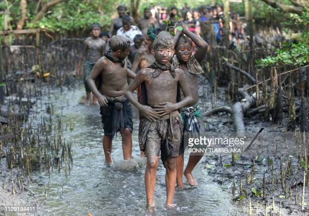 Balinese people put mud on their body during a traditional mud bath known as Mebuugbuugan in Kedonganan village near Denpasar on Indonesia's resort...