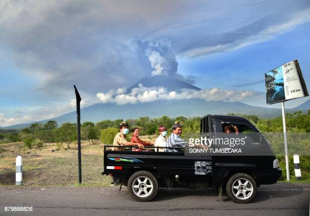 TOPSHOT Balinese people ride on an open car past Mount Agung erupting seen from Kubu subdistrict in Karangasem Regency on Indonesia's resort island...