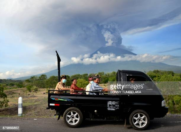 Balinese people ride on an open car past Mount Agung erupting seen from Kubu subdistrict in Karangasem Regency on Indonesia's resort island of Bali...