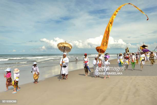 Balinese people take part in a Melasti ceremony prayer at Petitenget beach near Denpasar on Indonesia's resort island of Bali on March 14 2018...
