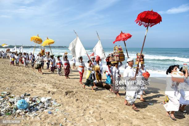 Balinese people walk along Kuta beach to attend prayers for the Melasti ceremony near Denpasar on the Indonesian resort island of Bali on March 25...