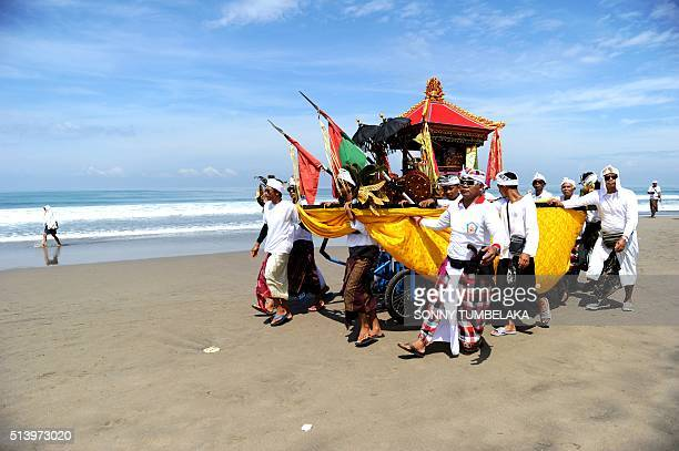 Balinese people walk along the beach for a Melasti ceremony prayer at Petitenget beach near Denpasar on Bali island on March 6 2016 Melasti is a...