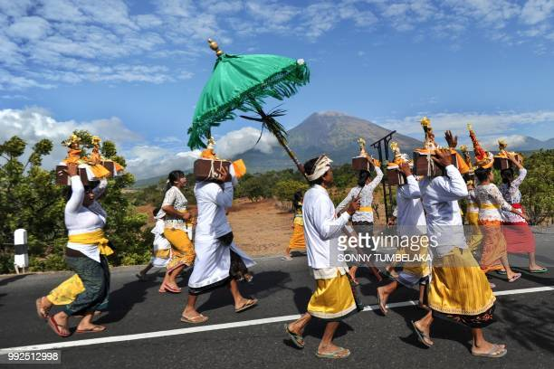 Balinese people walk before Mount Agung from Muntig village to the beach during a Melasti ceremony a purification ceremony and ritual in Karangasem...