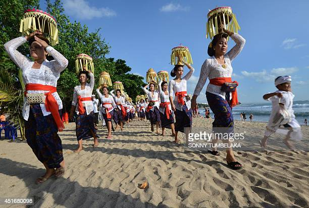 Balinese people walk near the beach during Melasti ceremony prayers in Kuta on Bali island on July 4 2014 During Melasti villagers dressed in their...
