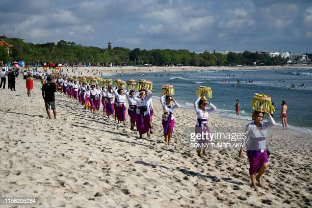 Balinese people walk on a beach for Melasti ceremony prayers in Kuta on Indonesia's resort island of Bali on July 28 2019 Melasti is a purification...