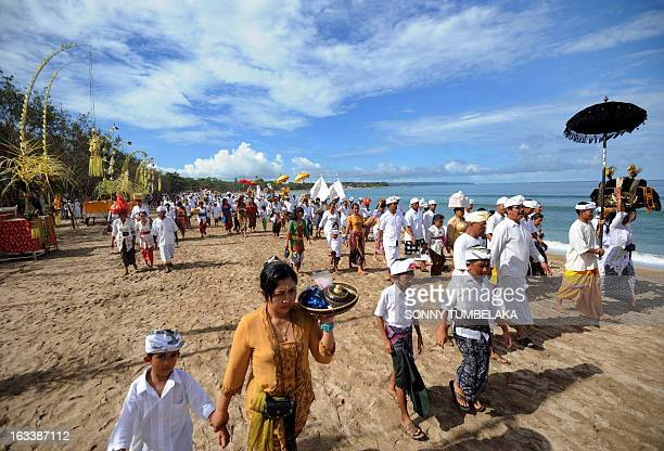 Balinese people walk with offerings during a Melasti ceremony at Kuta beach on Indonesia's resort island of Bali on March 9 2013 Melasti is a...