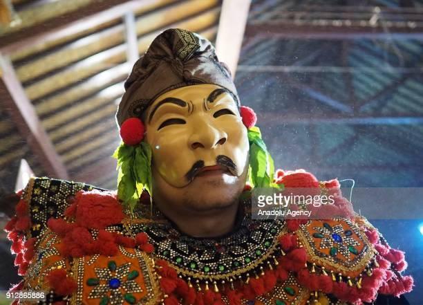 Balinese performer Mujasa puts on his second mask as a narrator for Sidakarya dance drama at Pura Desa Museum in Ubud regency of Bali Indonesia on...