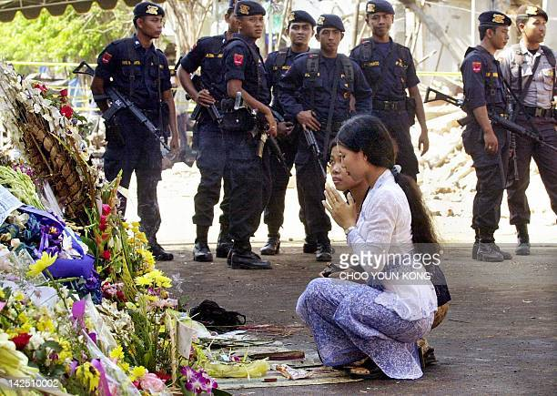 Balinese pray for the victims killed by a bomb blast at the site as armed police look on in the tourist district of Kuta Denpasar on Bali island 18...