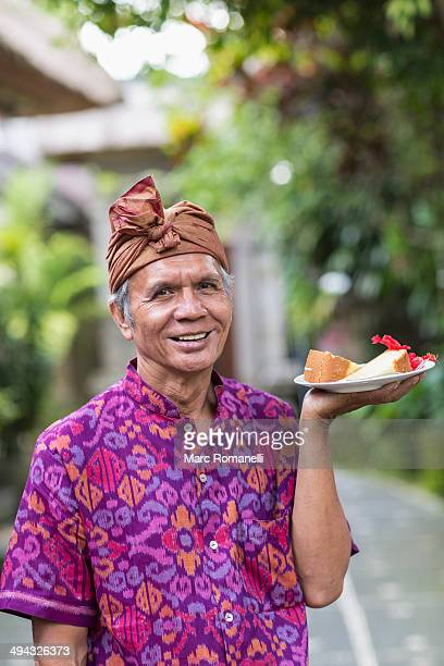 Balinese server carrying plate of food