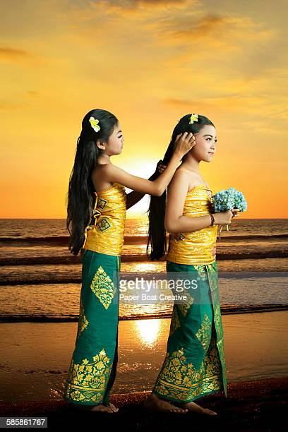 Balinese sisters fixing hair by the beach side