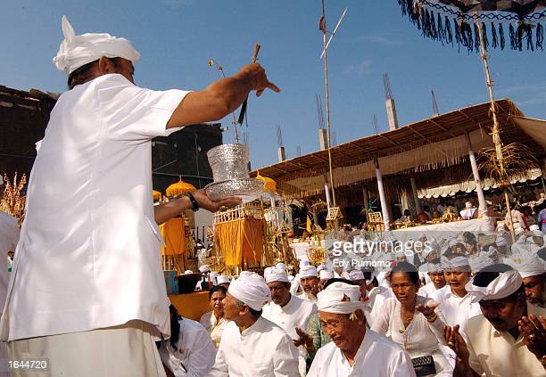 Balinese spiritual leader sprays holy water during a purification ceremony at the site of a deadly night club bomb blast November 15 2002 in Denpasar...