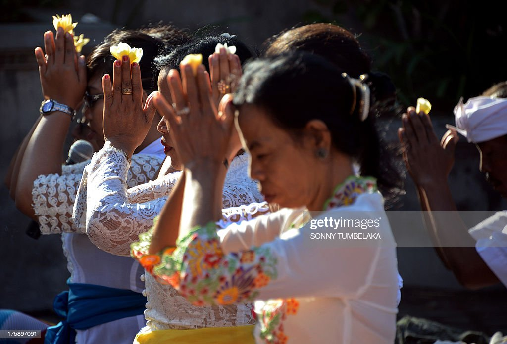 Balinese teachers pray during the Hindu Saraswati holy day at a school in Denpasar on Bali island on August 10, 2013. Hindu devotees in Bali celebrated Saraswati day - the day to worship God in his manifestation as the master of all knowledge.