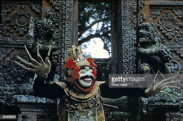 Balinese 'topeng' or masked dancer in ceremonial headdress stands in front of ornately carved doors His goved hands bear long fingernails