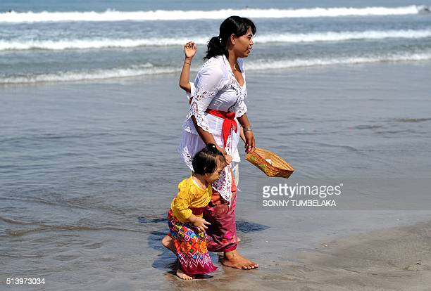 A Balinese woman attends a Melasti ceremony prayer with her children at Petitenget beach near Denpasar on Bali island on March 6 2016 Melasti is a...