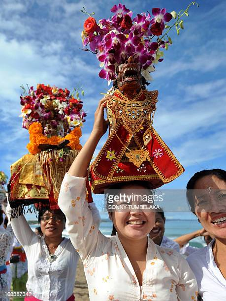 Balinese woman carry offerings on their heads during a Melasti ceremony at Kuta beach on Indonesia's resort island of Bali on March 9 2013 Melasti is...