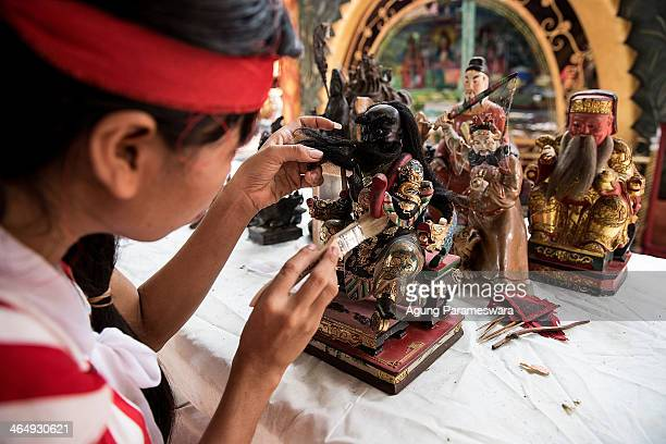 Balinese woman cleans statues during preparations for the upcoming Chinese New Year at Dwipayana Tanah Kilap Temple on January 25 2014 in Denpasar...