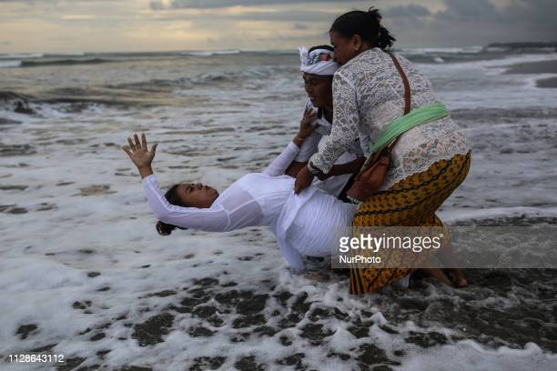Balinese woman in a trance gestures during the Melasti ritual ceremony at Batu Bolong beach in Bali Indonesia on March 4 2019 The Melasti ritual is...