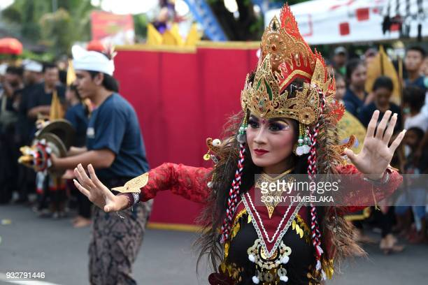 A Balinese woman performs a traditional dance during a parade ahead of the Day of Silence in Denpasar on Indonesia's resort island of Bali on March...