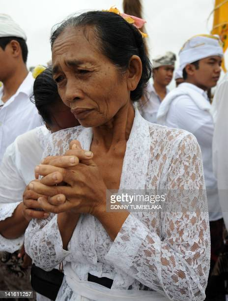 A Balinese woman prays during the Melasti ceremony prayer at Petitenget beach in Kuta on the island of Bali on March 20 2012 Melasti is a...
