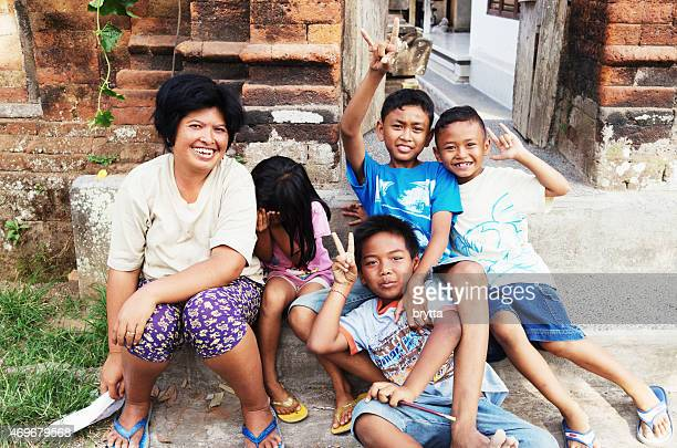 Balinese woman sitting with children in front of family compound