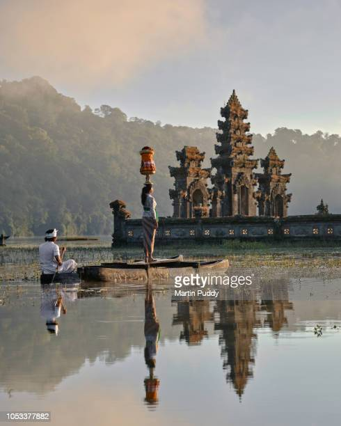 Balinese woman standing on dugout boat looking at Tamblingan temple