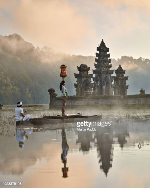Balinese woman standing on dugout boat looking at Tamblingan temple at sunrise