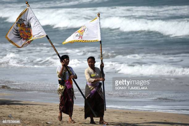 Balinese women carry flags as they walk along Kuta beach to attend prayers for the Melasti ceremony near Denpasar on the Indonesian resort island of...