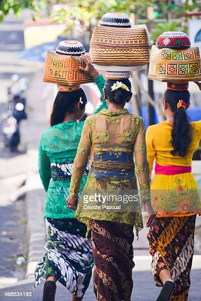 Balinese women in festive attire on Galungan day carrying gifts and offerings on their heads. Galungan day is one of Bali's most important religious...