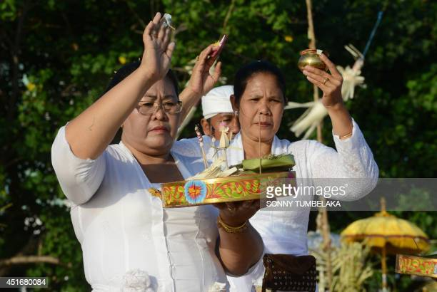 Balinese women pray near the beach during Melasti ceremony prayers in Kuta on Bali island on July 4 2014 During Melasti villagers dressed in their...